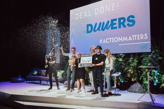 Henkilöitä vastaanottamassa palkintoa esiintymislavalla.