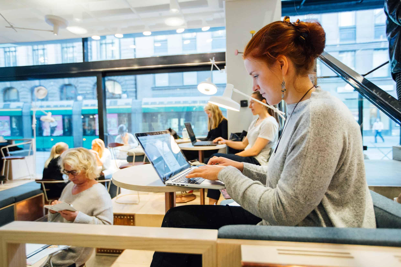 Nainen kirjoittamassa kannettavalla tietokoneella.