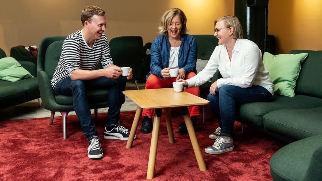 Kolme yrittäjää juomassa kahvia.