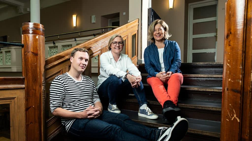 Kolme yrittäjää istumassa portailla.