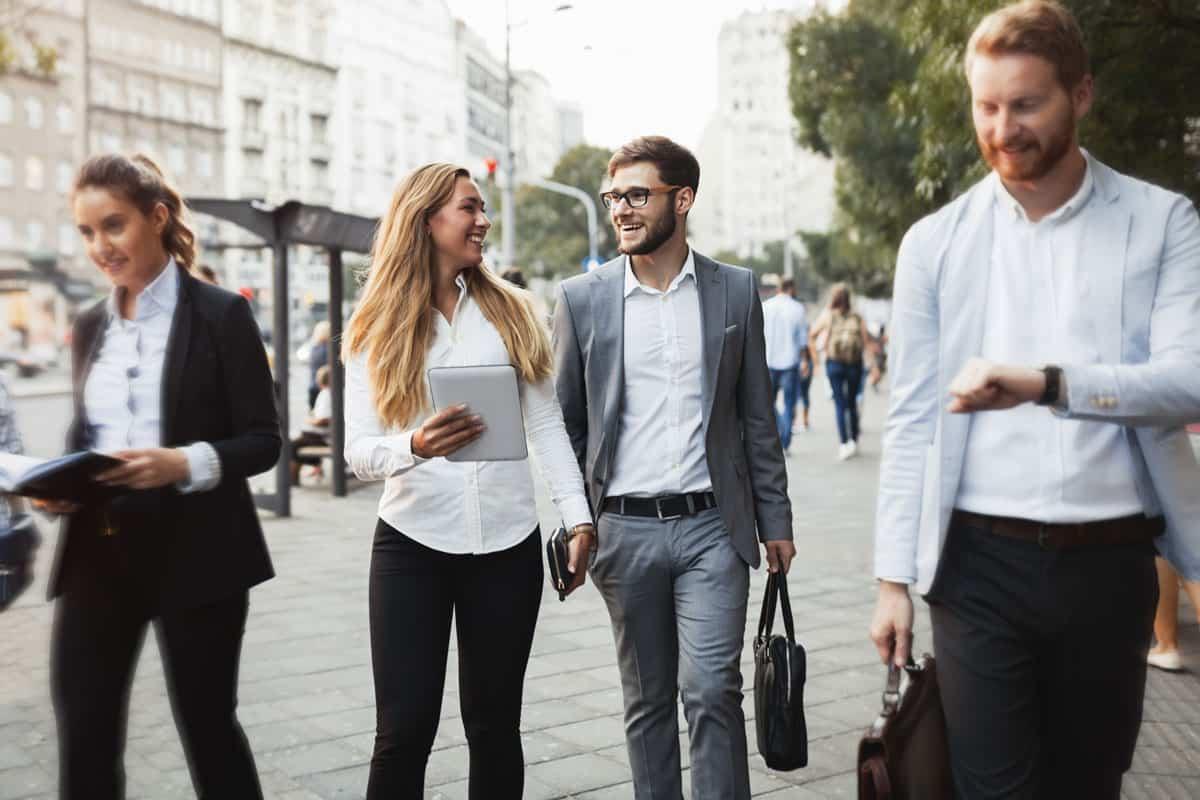 Neljä yrittäjää kävelemässä ulkona.