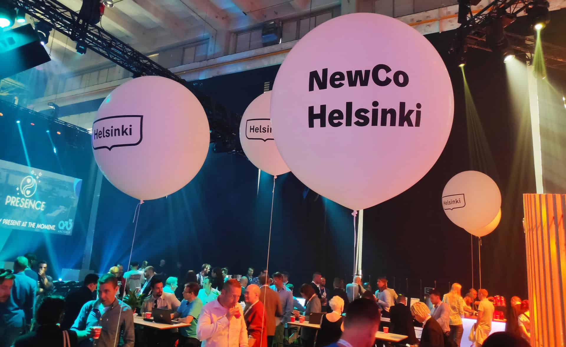 Big balloons with the logos of the City of Helsinki and NewCo Helsinki, at an event.