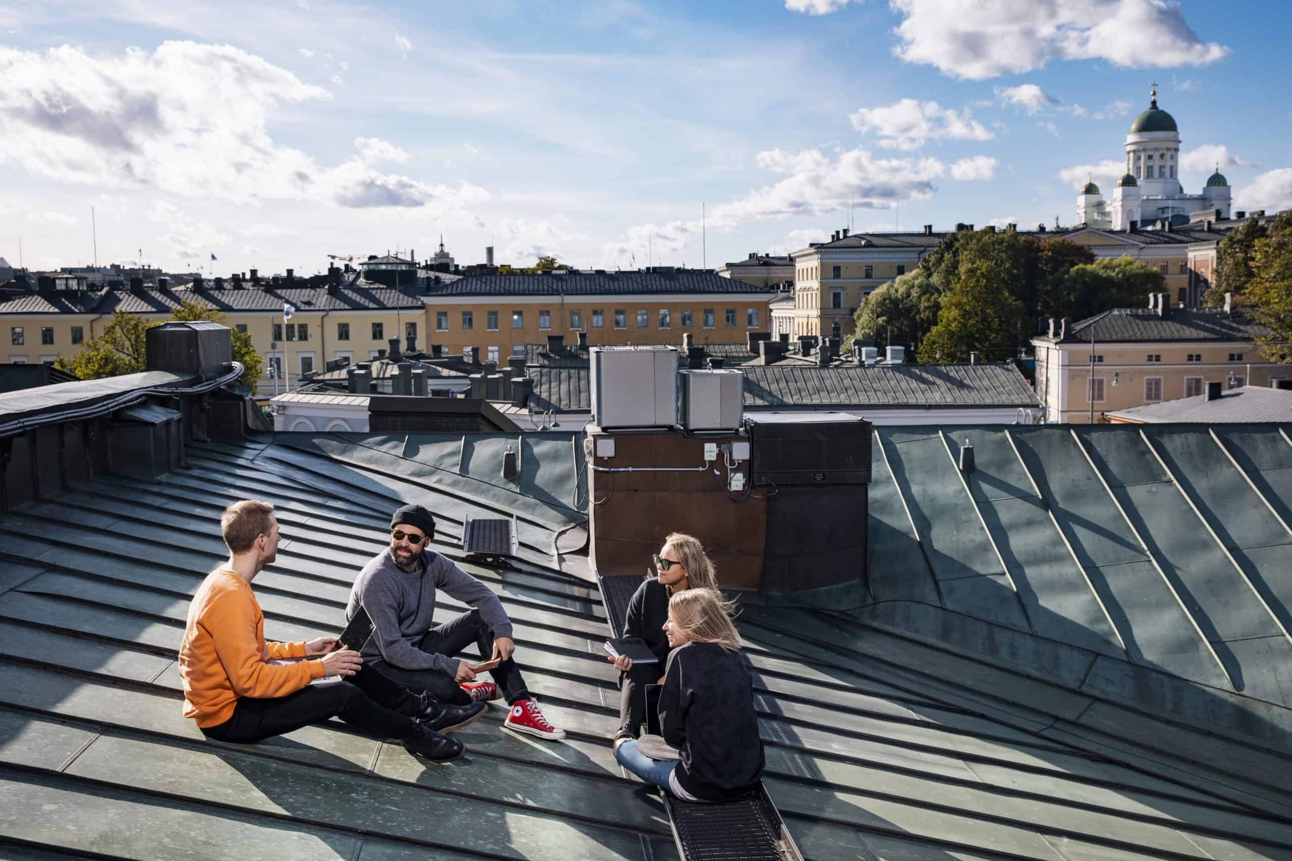 Four people are sitting on a roof.