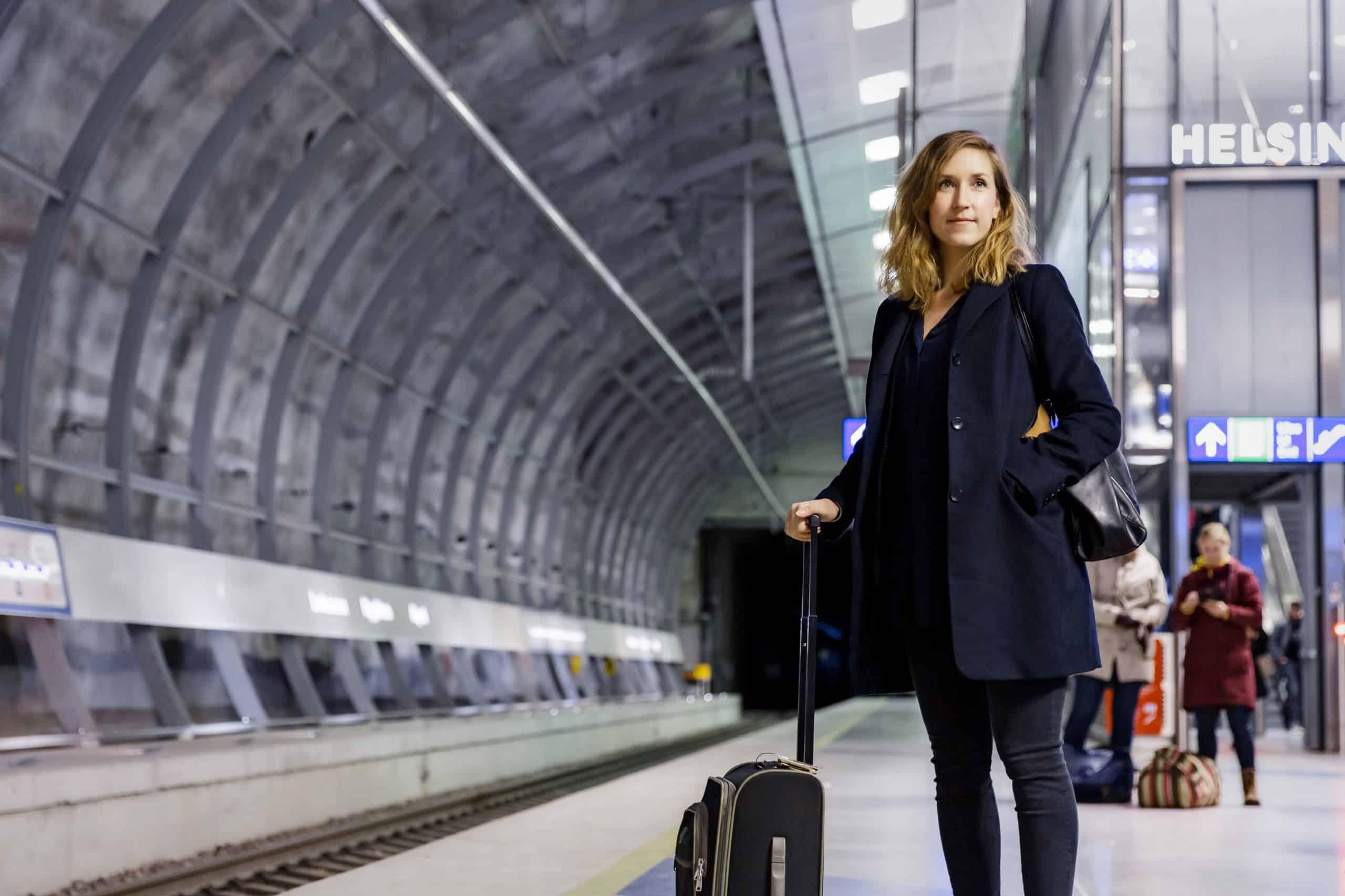 Nainen matkalaukun kanssa juna-asemalla.