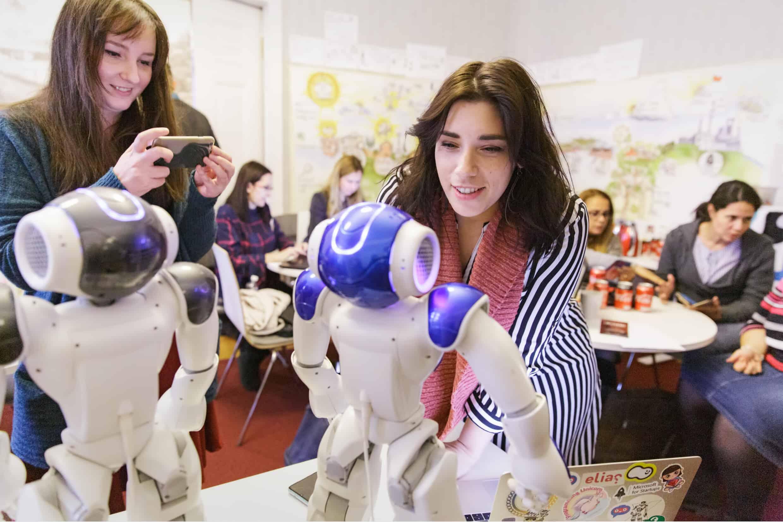 Kaksi naista katsoo pöydällä olevia robotteja.
